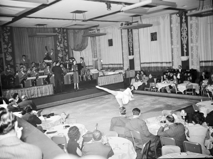 Skater Alice Farrar performs on an indoor ice rink, surrounded by people seated in tables and chairs at the Terrace Room, with a full band and singer in the background..