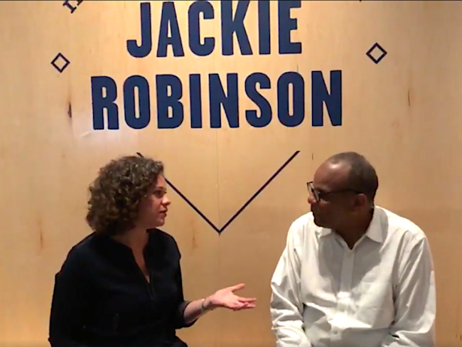 "A man and woman sit in front of signage for the exhibition ""In the Dugout with Jackie Robinson: An Intimate Portrait of a Baseball Legend."""
