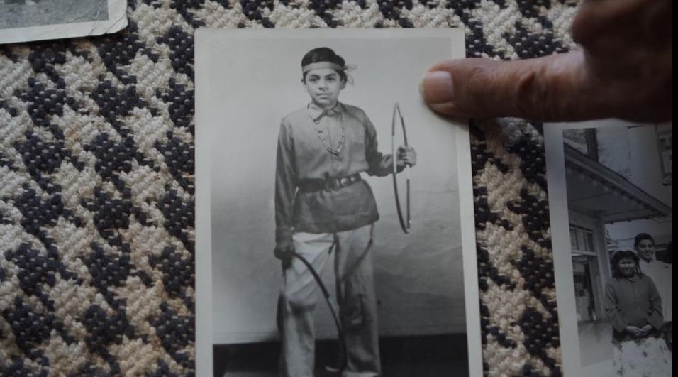 photographie en noir et blanc d'un jeune garçon autochtone tenant un cerceau dans la main gauche et un autre cerceau autour de la jambe droite. Un doigt pointe la photo.