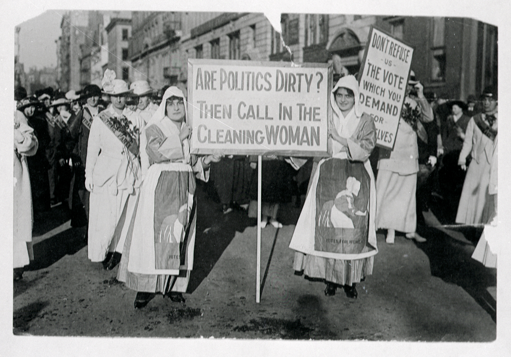 """During a suffrage rally two women face the camera with a sign that says """"Are politics dirty? Then call in the cleaning woman"""""""