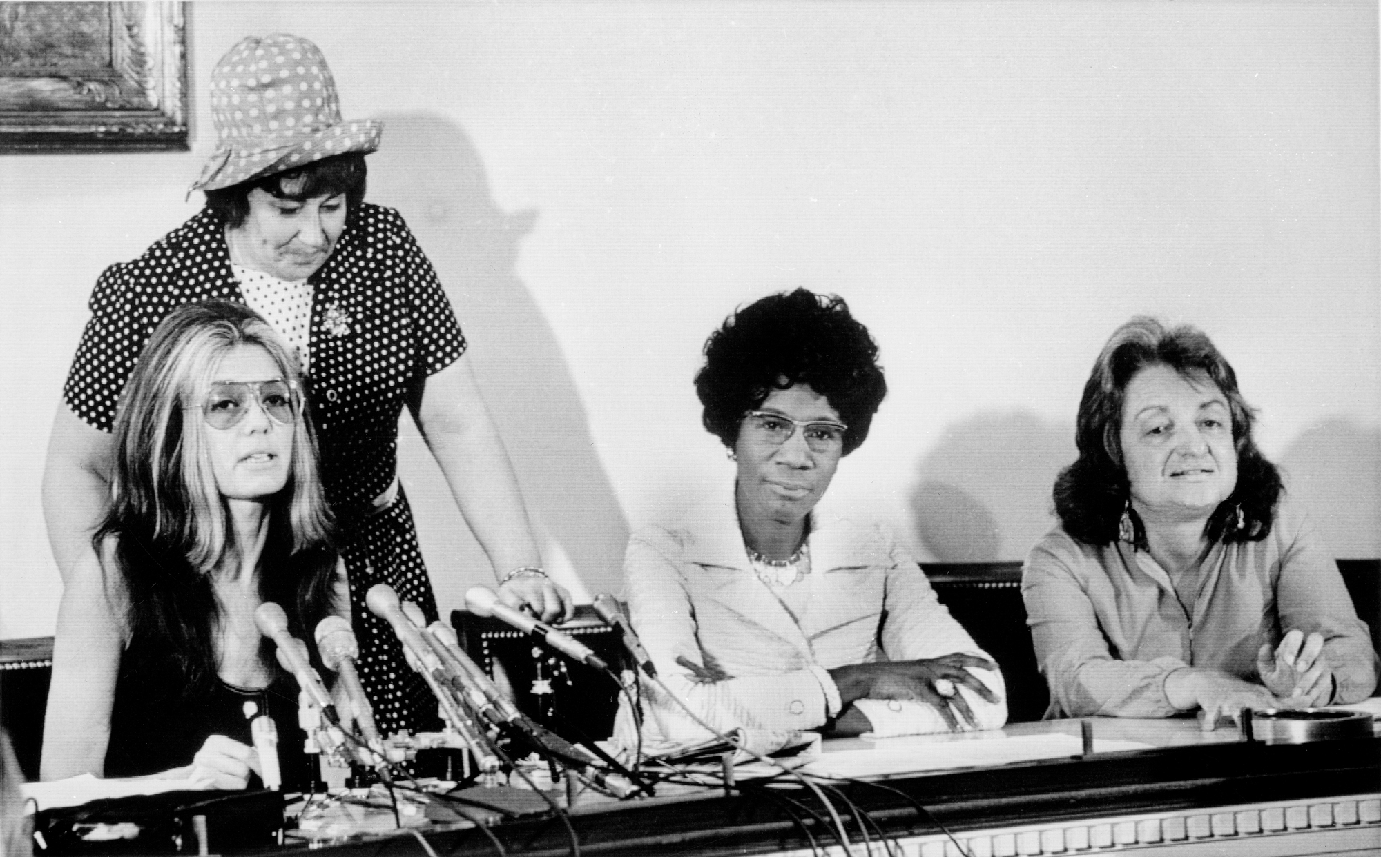 Three women sit at a table, one has microphones in front of her, suggesting it is a press conference