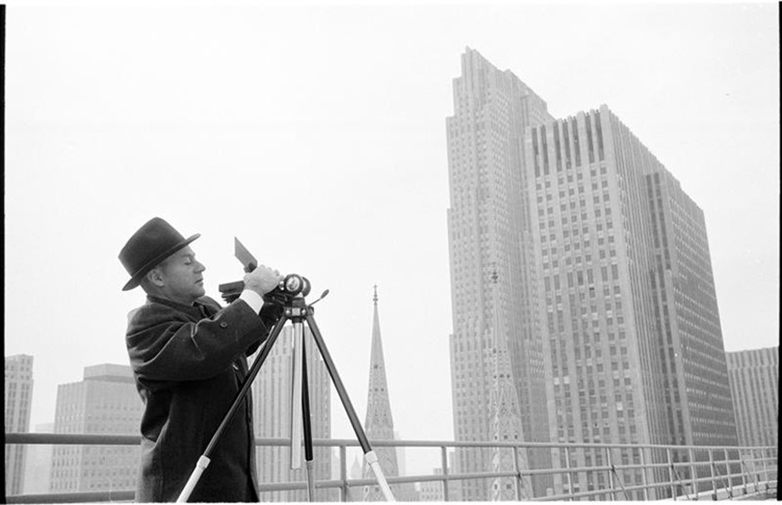 Man adjusting his camera on a tripod with the New York City skyline in the background.