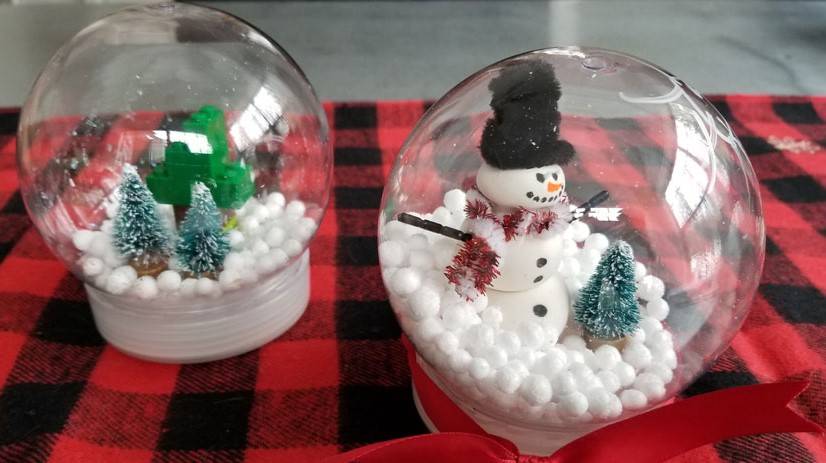 Image of two snow globe crafts. A winter scene with evergreen trees to the left, and a snowman and tree to the right.