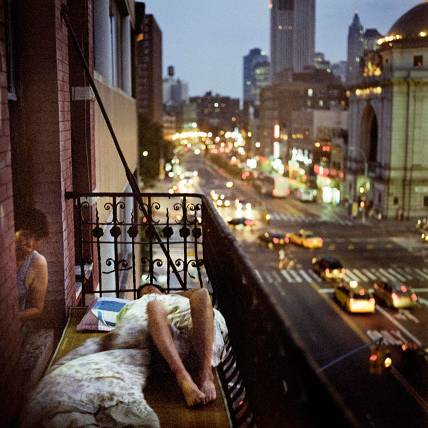 A person lies on the terrace of an apartment building, while a man leans out a window to look at the camera