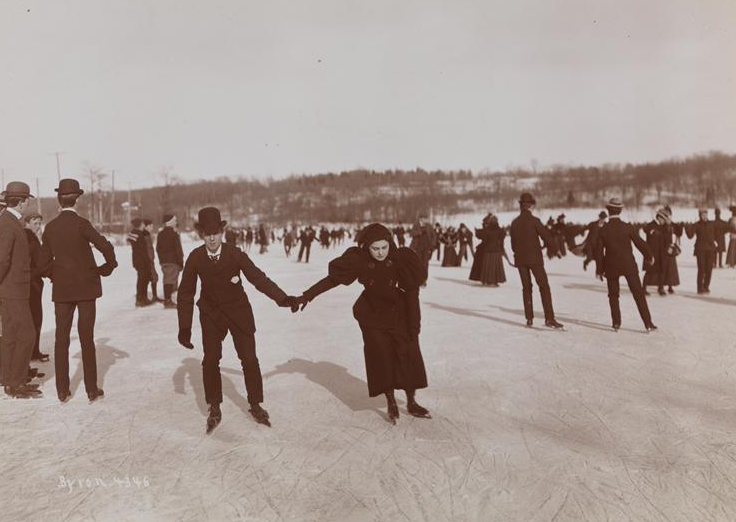 A man and women hold hands while ice skating among a group of people outdoors.