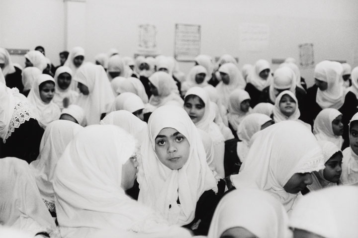 A group of girls wearing hijabs stand in a schoolyard, one girl in the middle stares into the camera