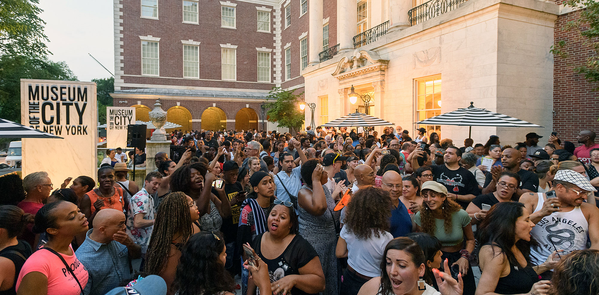 People attending a summer outside party at the Museum of the City of New York