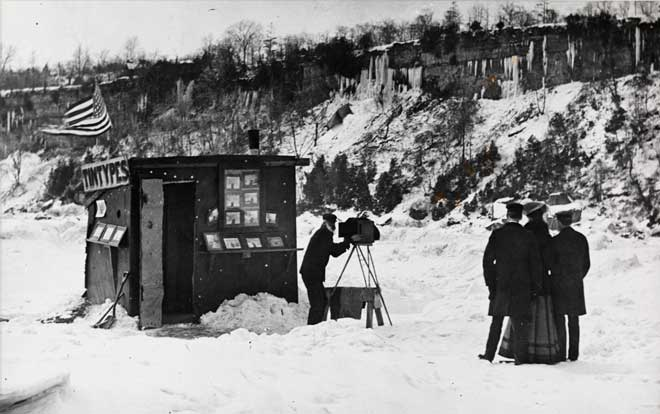 A photographer takes a photograph of a couple in the snow outside of a tintype booth