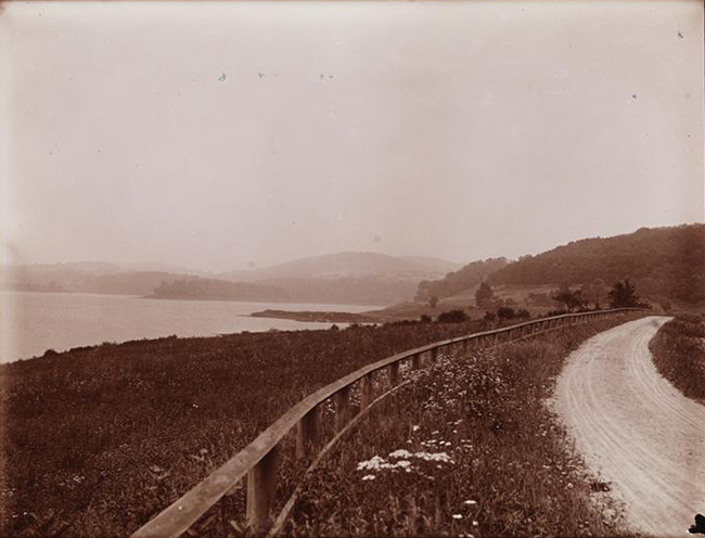 Black and white photograph showing a dirt road, a hillside leading down to Croton Lake, and mountains in the distance.