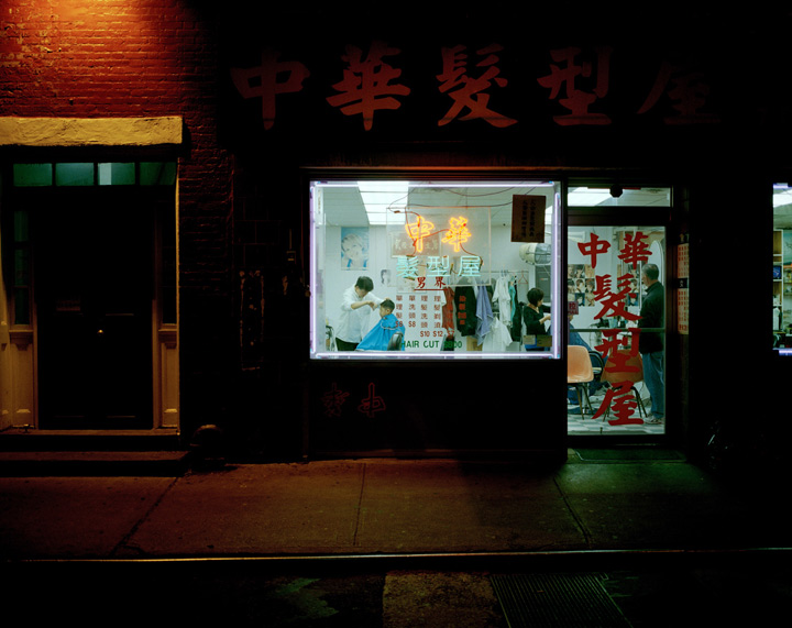 Taken from the street, a boy is seen getting his hair cut in a Chinese barbershop. The signs for the shop are in Chinese.