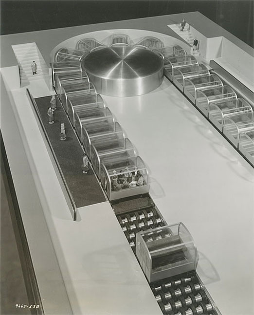 Close-up of working model of conveyor subway system, shows passengers entering and riding in passenger cars.