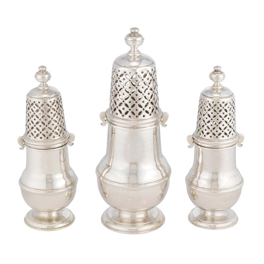 Three silver sugar casters, objects used like salt shakers for sugar. The middle caster is larger than the other two