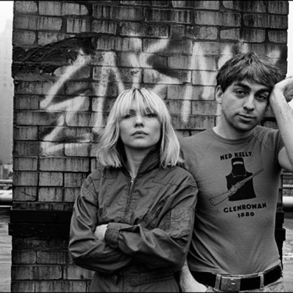Fotografia preto e branco de um homem e uma mulher em pé no telhado, de frente para a câmera. A mulher está com os braços cruzados, o homem levanta a mão na têmpora.