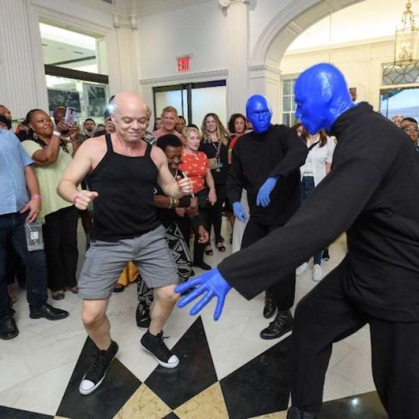 Três homens azuis (do Blue Man Group) dançam no saguão do museu com os visitantes durante o Uptown Bounce em agosto de 2019.