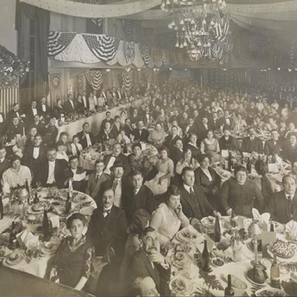 Preto e branco por volta de 1910 fotografia de um banquete formal de jantar. Homens, mulheres e algumas crianças sentam-se nas mesas olhando para a câmera, os ajustes de lugar, a sobremesa e as garrafas de vinho são visíveis nas mesas.
