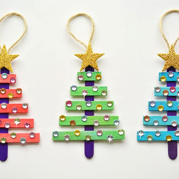 Red, green, and blue ornaments made from popsicle sticks and decorated with gemstones.