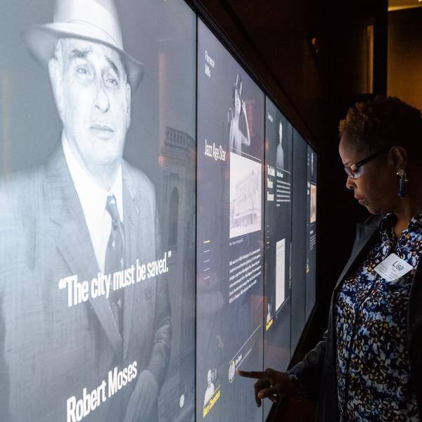 Photograph of an educator examining stories of New Yorkers from the 20th century in the World City gallery.