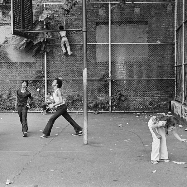 Photographie de personnes jouant au basket-ball dans un terrain de basket entre deux bâtiments, femme et enfant devant