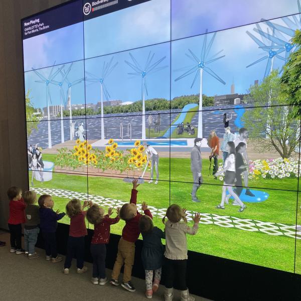 Ocho niños pequeños se paran frente a una pantalla de altura de pared. La pantalla presenta animaciones de molinos de viento, flores amarillas, hierba verde, agua azul y varios follajes. La gente camina por la pantalla y tiende a las plantas. Los niños pequeños alcanzan y tocan varias partes de la pantalla.