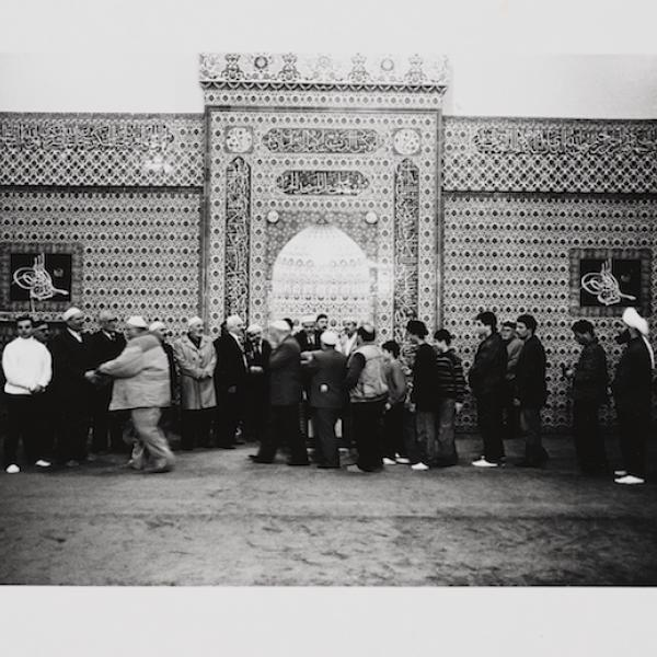 Un grupo de hombres musulmanes de varias edades, se reúnen fuera de una mezquita en Brooklyn. Se saludan y hacen cola.