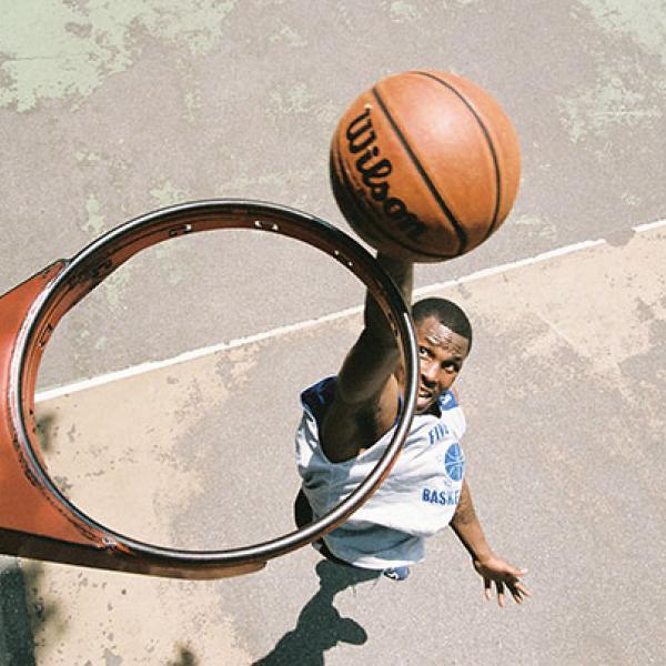 Vista de cima de uma cesta de basquete sem rede, onde um jogador é visto prestes a enterrar uma bola de basquete no aro