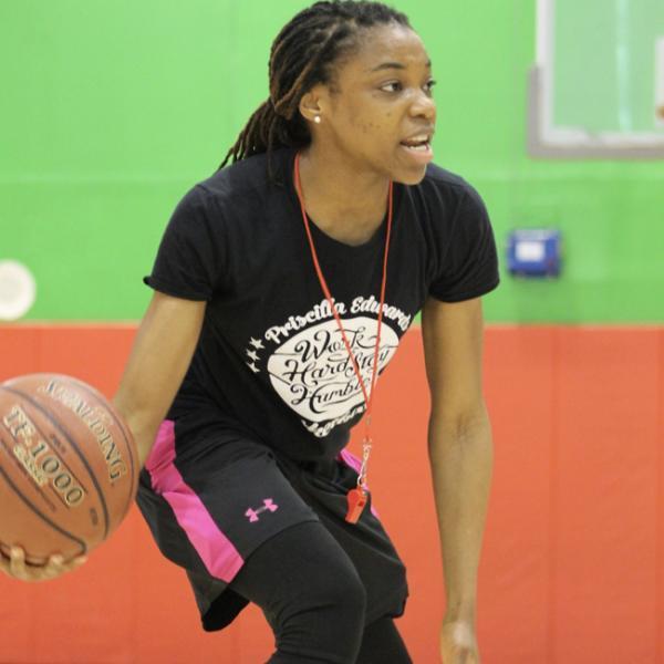 Priscilla Edwards sostiene una pelota de baloncesto en su mano derecha, en una posición de goteo bajo, se enfrenta a un grupo fuera de cámara, hablando con ellos.