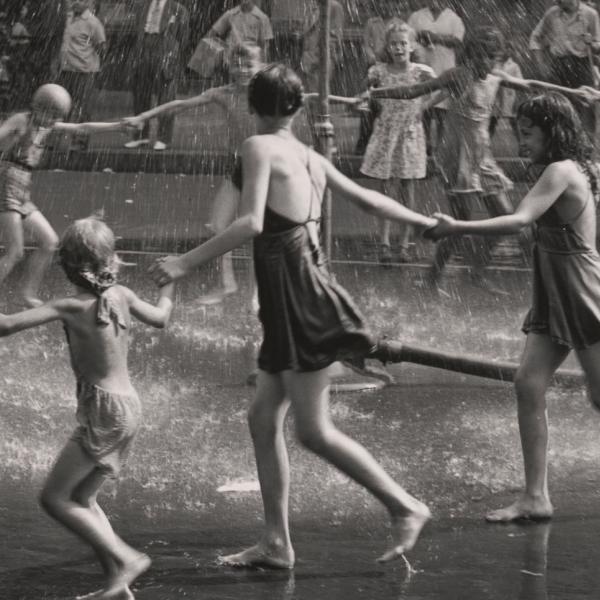 Um grupo de crianças e adolescentes de mãos dadas em círculo enquanto correm em volta de um aspersor de playground