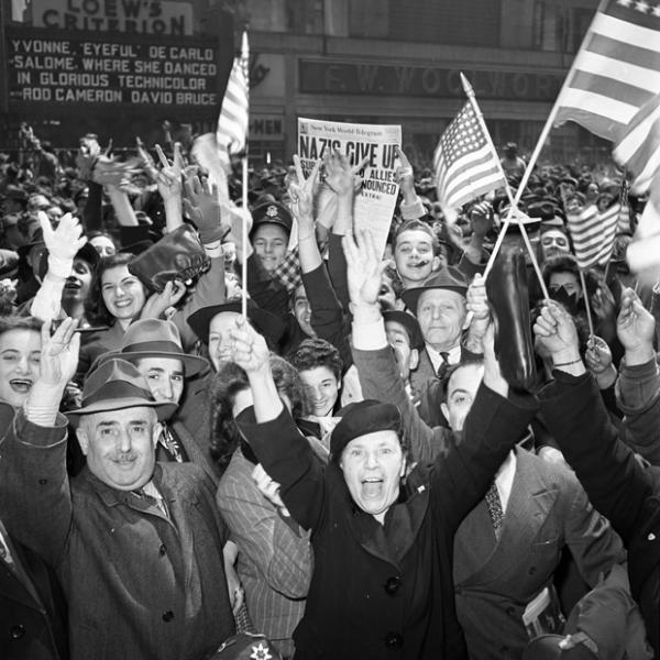 A crowd of men and women on Broadway in Manhattan hold American flags and throw their arms up celebrate the end of World War II in Europe.