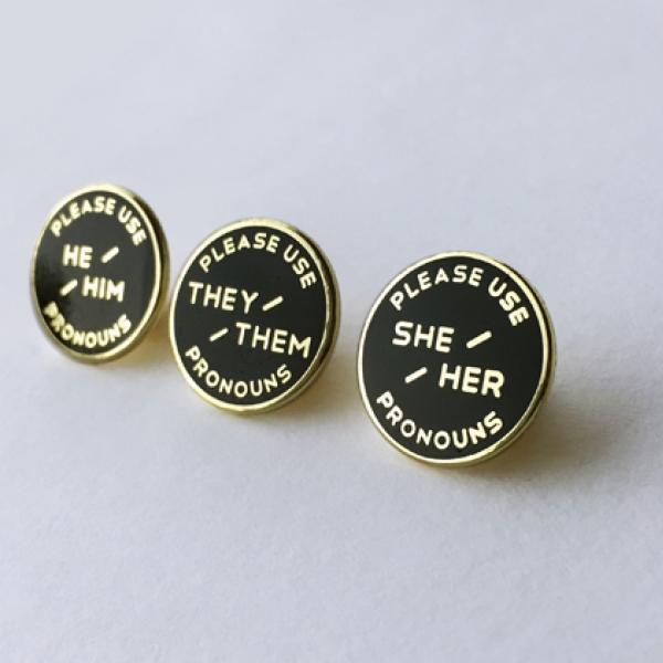 Três pinos de pronome esmaltado. Fundo preto com texto de ouro.