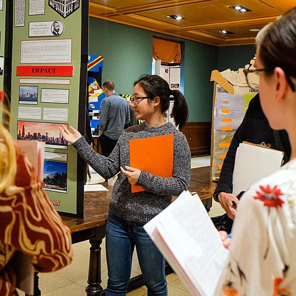 A student explains their project board as History Day judges look on during New York City History Day 2019.