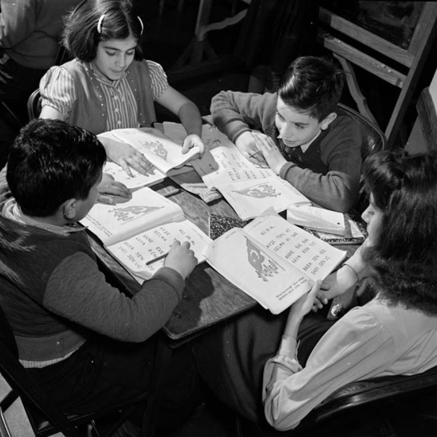 Four children sit around a table looking at the books in front of them