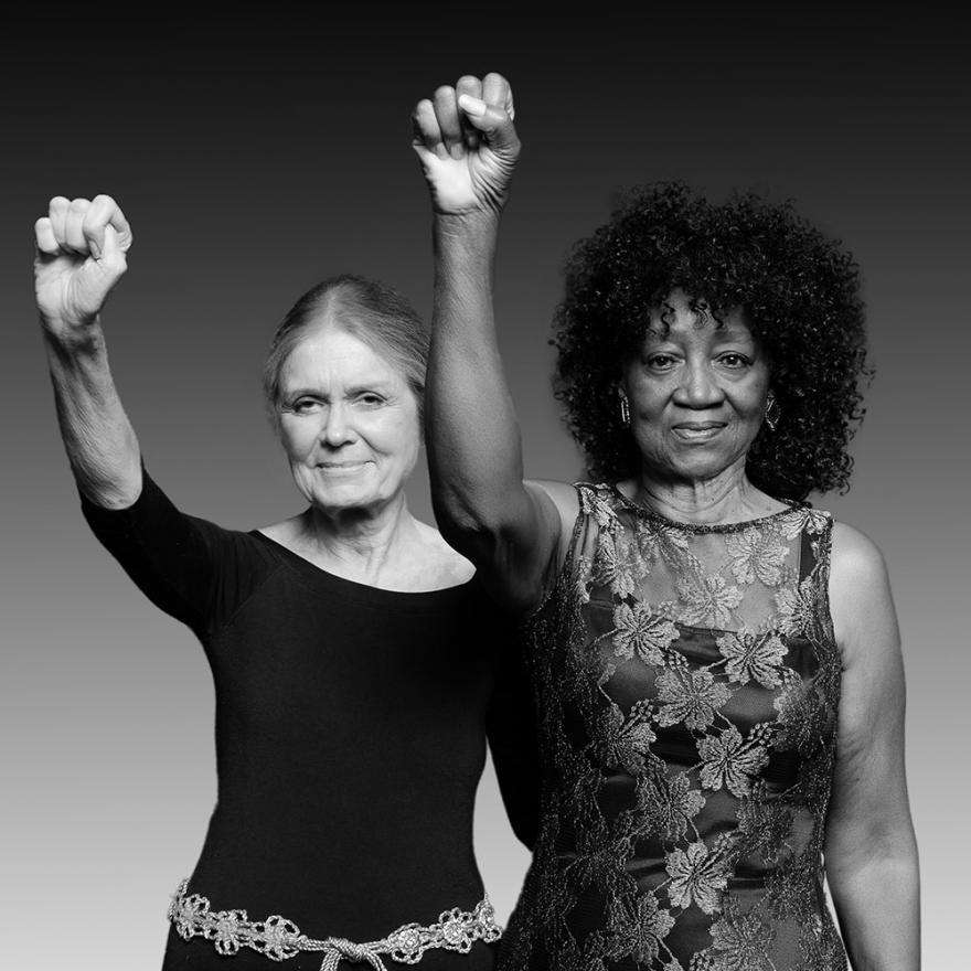 Two older women face the camera, each of their right arms are raised in a fist