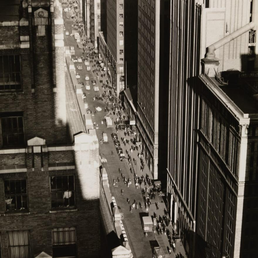 """View of a street in New York City that's surrounded on both sides by tall buildings, creating a """"canyon"""" with the street"""