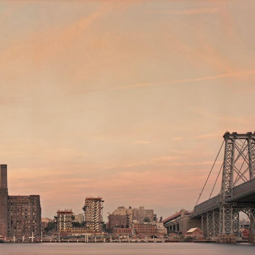 bridge and series of buildings on the waterfront are lit by an orange-purple sunset