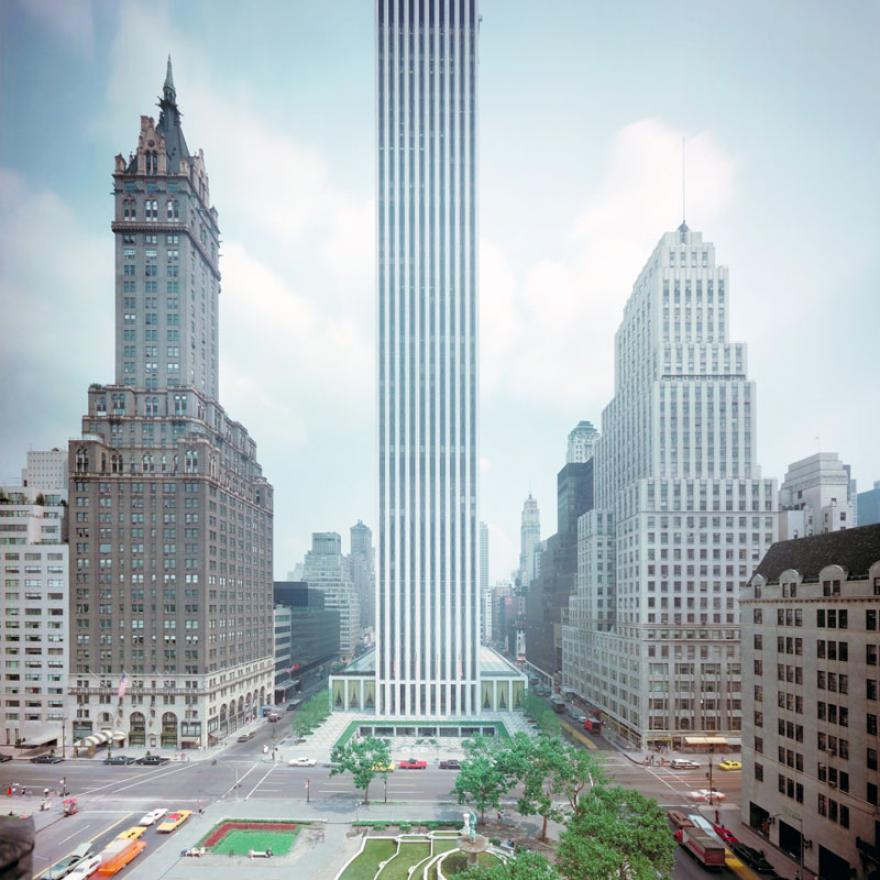 A building towers over its neighbors as it takes up a full block in New York City. In front of the building is a park