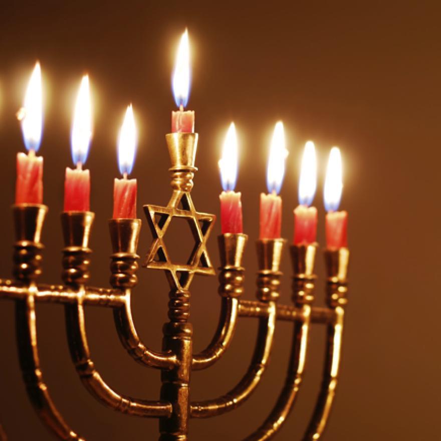 A Hanukkah menorah with all candles lit.