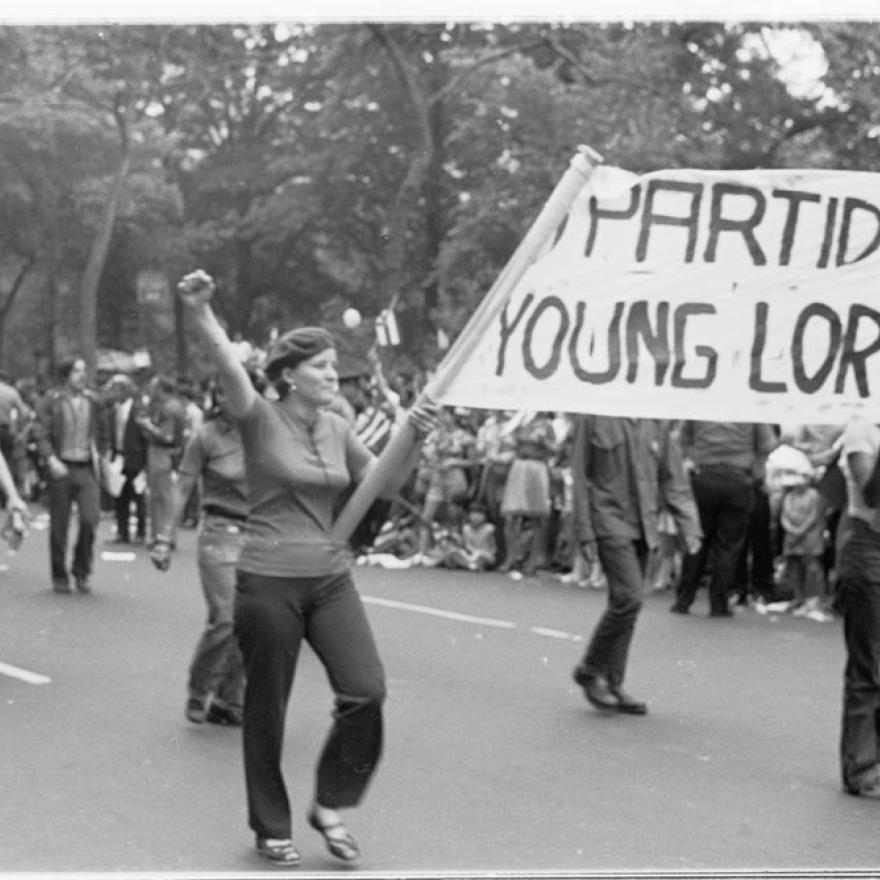 "People march during a parade, while two hold a sign between them that says ""_PARTIDO/YOUNG LORD"""