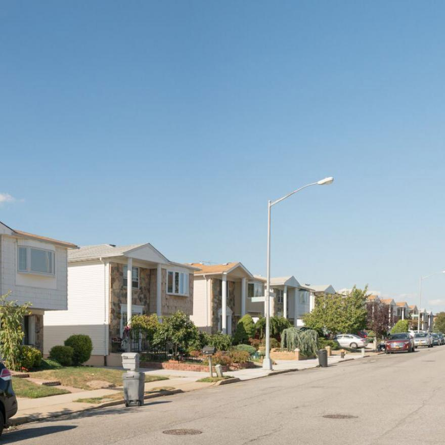 A series of identical two-story houses line a street