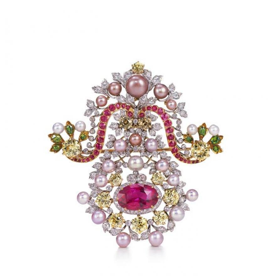 Brooch made of a metal backing with pink, yellow, and green diamonds, pink and white pearls, and silver leaves