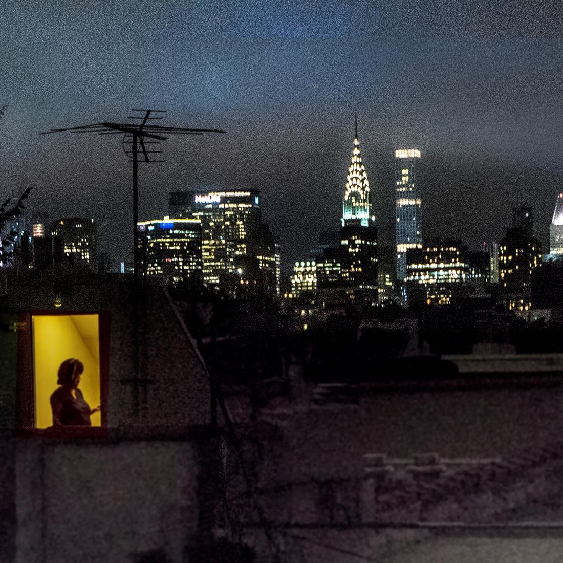 Vista trasera del apartamento de Sally Davies en East 5th Street por la noche con ventanas iluminadas.