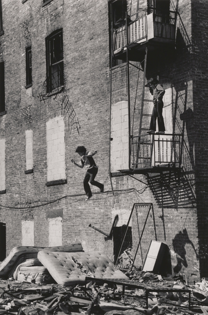 Black and white photograph of a brick building. A boy stands on the railing of a fire escape looking down at another boy who is captures mid-air before he lands on a pile of old mattress.