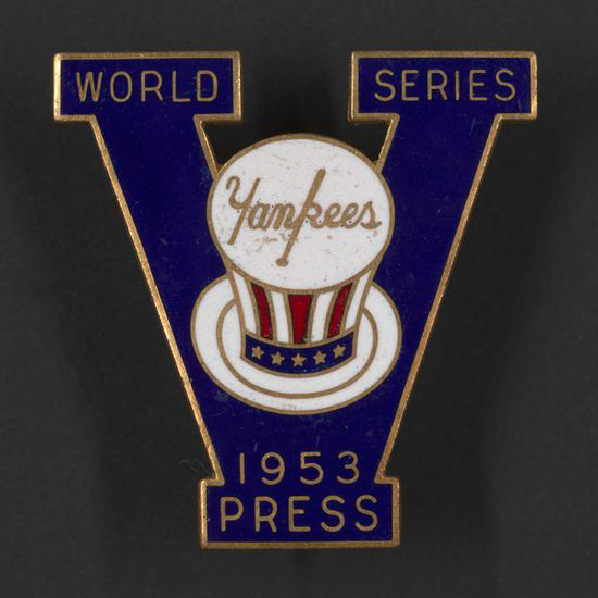 "Enamel pin in the shape of the letter ""V."" Top left of ""V"" says ""World,"" and top right says ""Series."" At center is Yankees logo on stars and stripes top hat. At the bottom, ""1953, Press."""