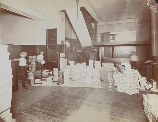 Interior da sala de estoque da loja Rogers Peet & Co., com dois homens trabalhando e caixas empilhadas ao redor.