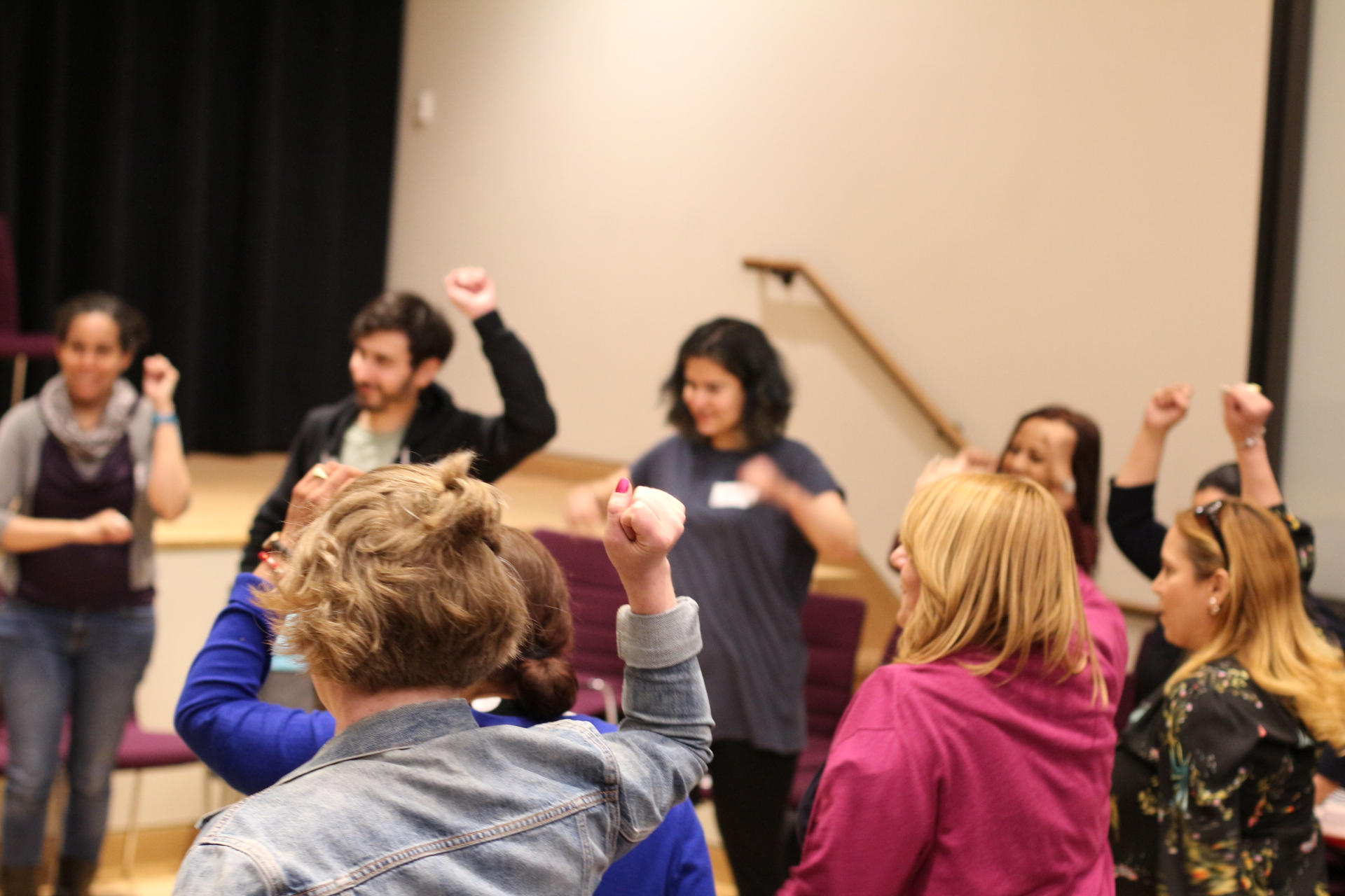 Educators standing in a circle, fists raised, participating in a workshop at the 2018 teaching social activism conference.
