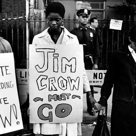 """Uma mulher está de pé em uma fila de manifestantes de mãos dadas, com uma placa ao redor dizendo """"Jim Crow deve ir"""""""