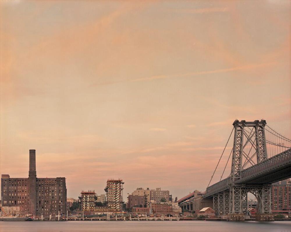 El puente y la serie de edificios en el paseo marítimo están iluminados por una puesta de sol naranja-púrpura