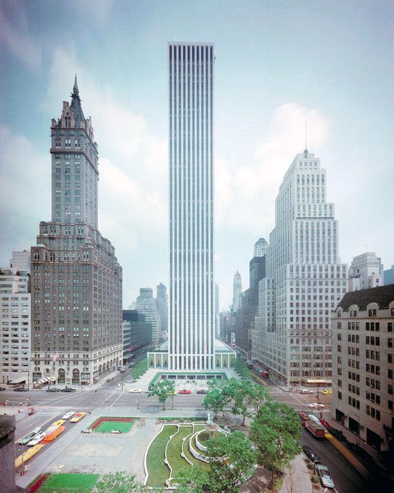 Un edificio se eleva sobre sus vecinos, ya que ocupa un bloque completo en la ciudad de Nueva York. En frente del edificio hay un parque
