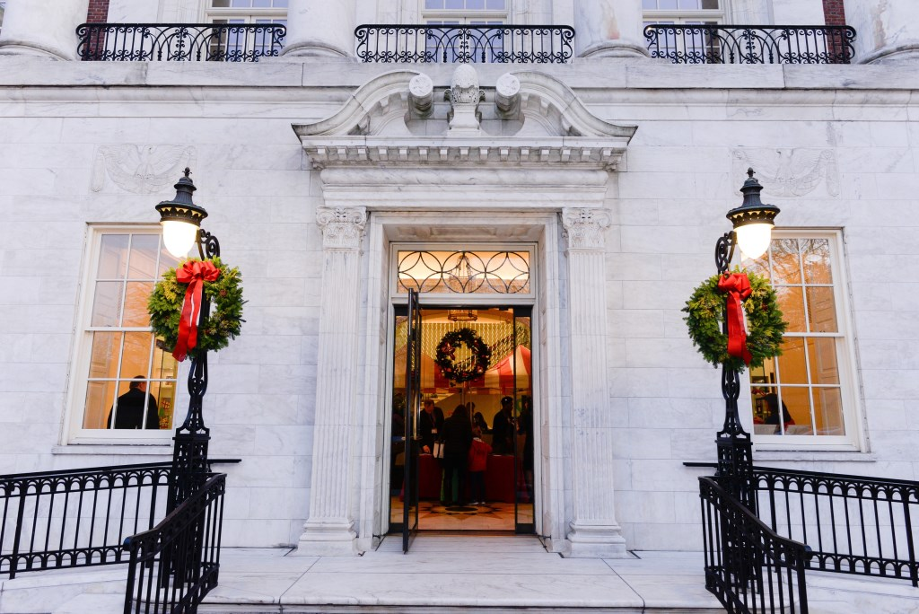The front entrance of the Museum of the City of New York with a wreath on the door and on two lamp posts on either side.