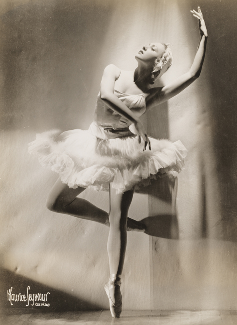 A ballerina, in costume, stands en pointe with one leg half bent at the knee and her arms raised.