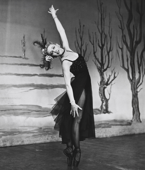 A ballerina, in costume, stands en pointe with one arm raised straight above her head, in front of a set backdrop with a line of barren trees.
